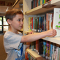 Elementary student pulls book off library shelf